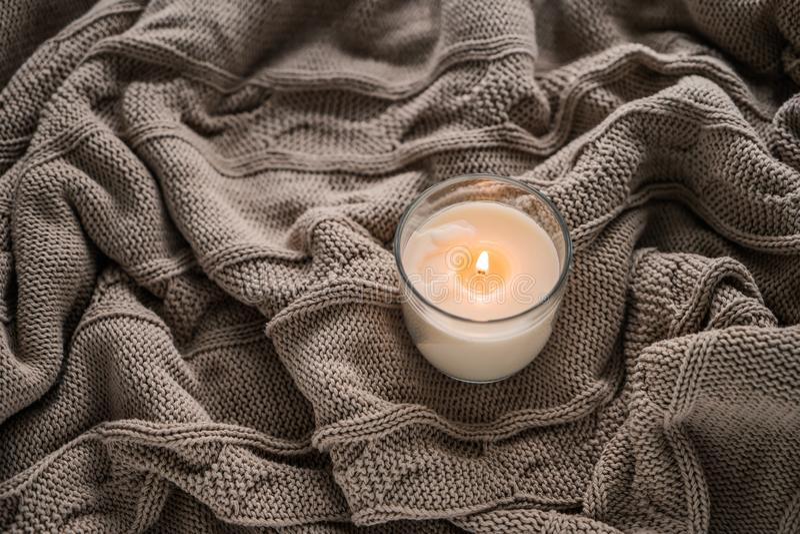 在温暖的格子花呢披肩的美好的灼烧的蜡烛 免版税库存图片