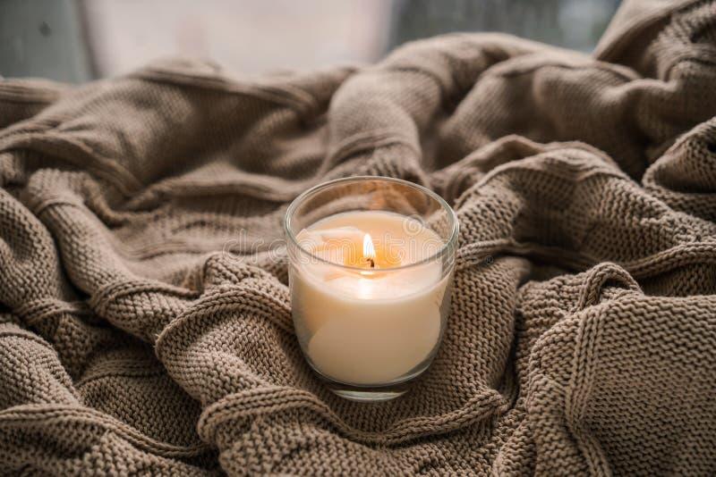 在温暖的格子花呢披肩的美好的灼烧的蜡烛 库存图片