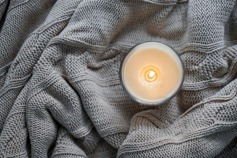 在温暖的格子花呢披肩的美好的灼烧的蜡烛 免版税图库摄影