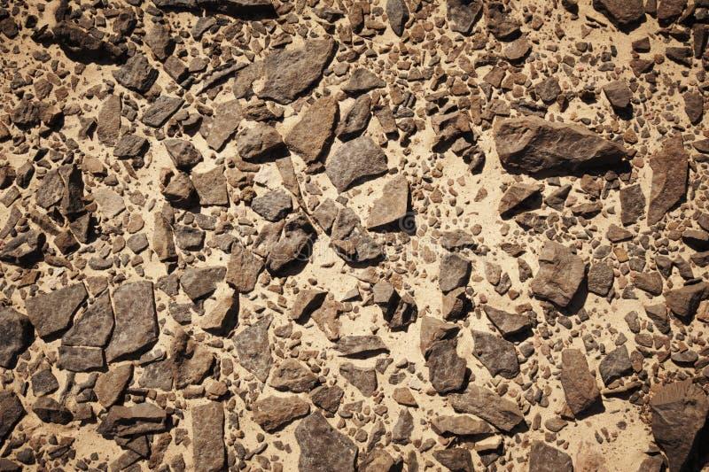 在温暖的沙子的石头在沙漠 库存图片