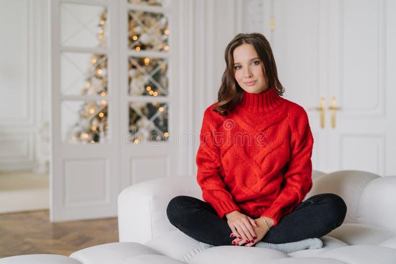 在温暖的红色被编织的毛线衣穿戴的轻松的主妇水平的射击,在莲花姿势的盘的腿坐长沙发,在spaciouss r 免版税库存照片