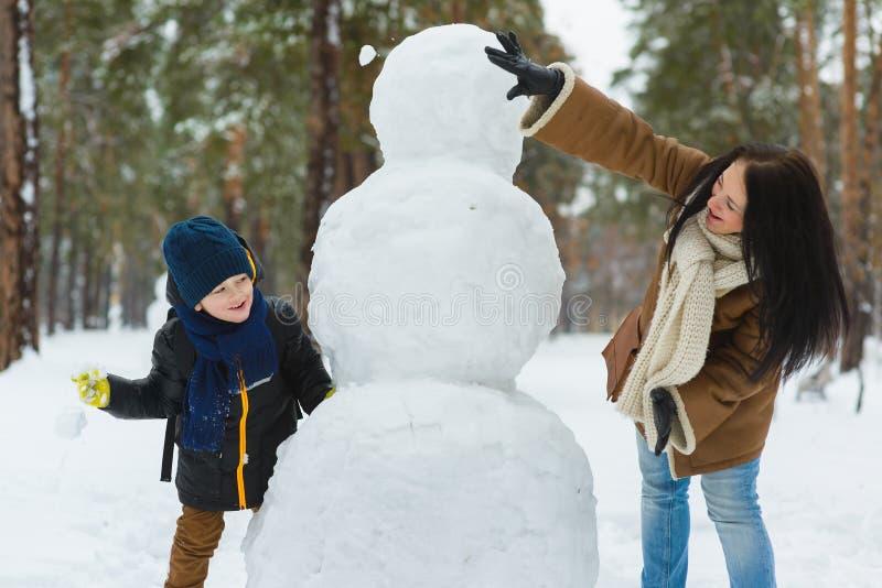 在温暖的衣物的愉快的家庭 微笑的母亲和儿子在室外的雪人旁边演奏雪球 冬天的概念 库存图片