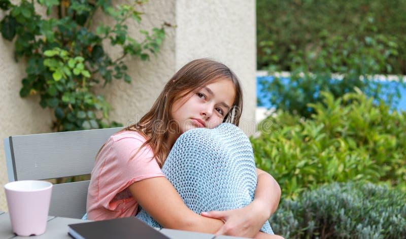 在温暖被编织的格子花呢披肩作白日梦的坐包裹的美丽的少年女孩外面 库存图片