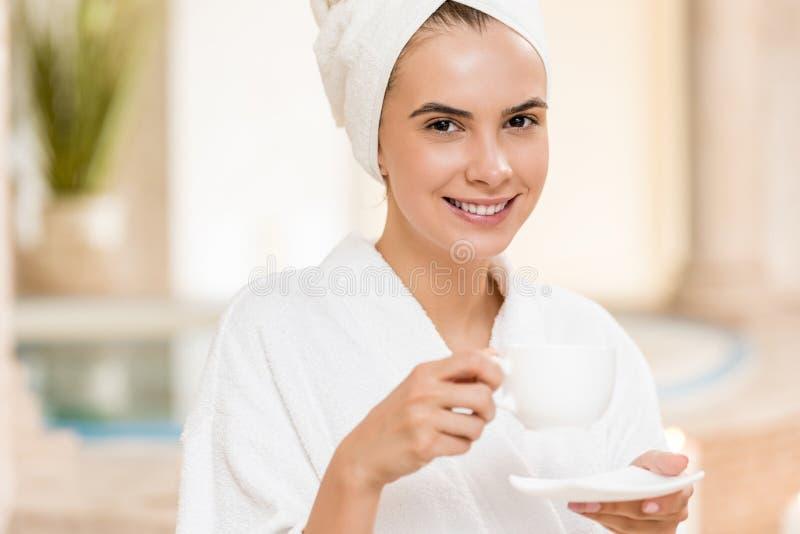 在温泉以后的妇女饮用的茶 库存图片