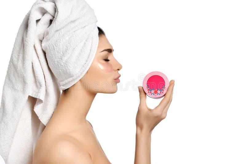 在温泉做法举行桃红色瓶子的愉快的俏丽的妇女面霜在白色背景的眼睛补丁以后 库存照片