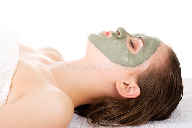 在温泉沙龙的秀丽治疗。有面部黏土面具的妇女。 免版税库存照片