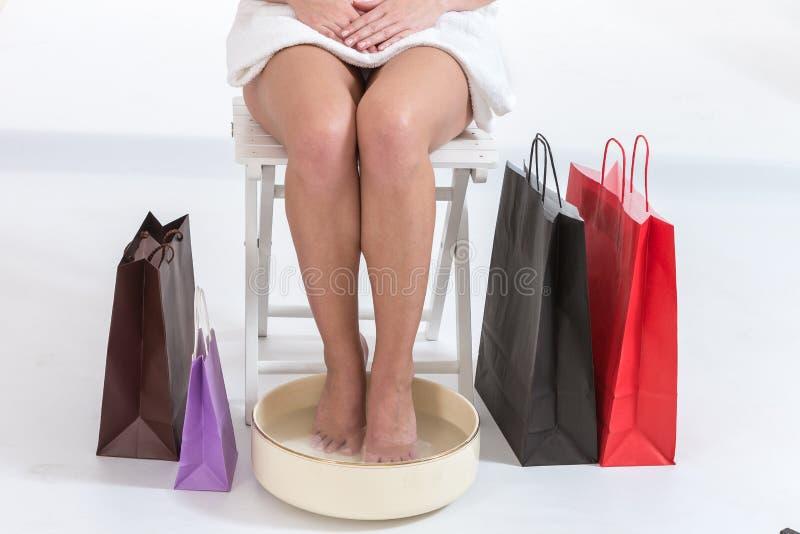 在温泉的女性脚用水滚保龄球在长的购物以后 免版税库存图片