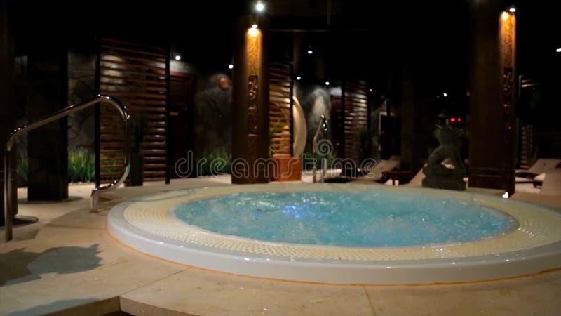 在温泉的放松水池与瀑布 与极可意浴缸和游泳池的空的豪华温泉 在蒸汽浴的极可意浴缸 健康 库存图片