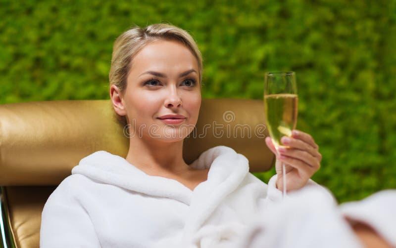 在温泉的美丽的少妇饮用的香槟 免版税图库摄影