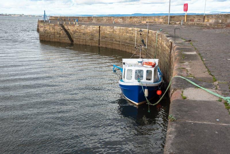 在港口和多云天空的小渔船 免版税库存图片