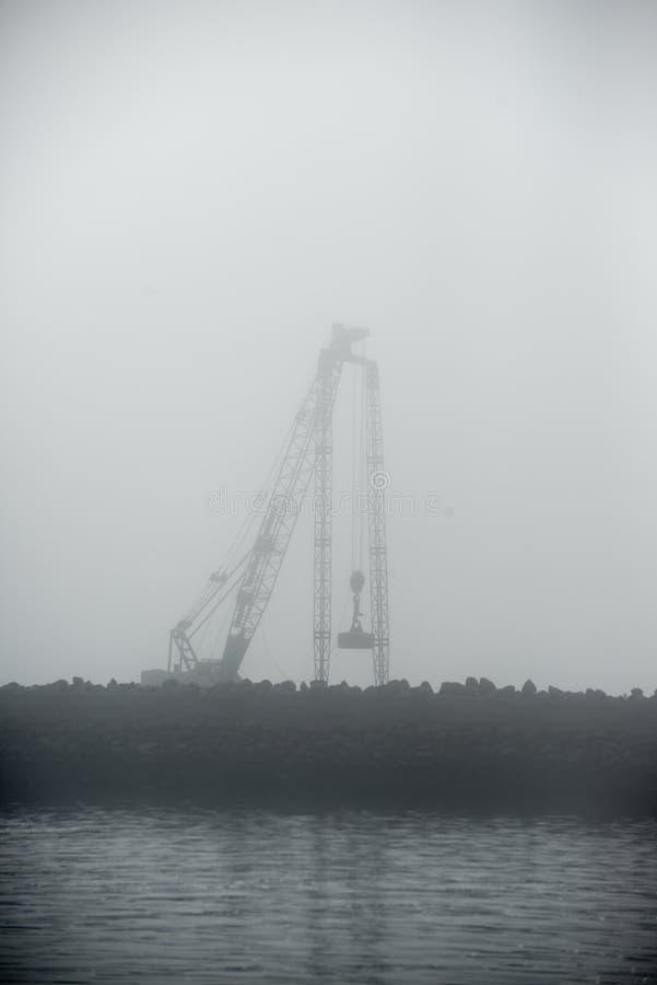 在港口薄雾的变紧密的起重机 库存图片