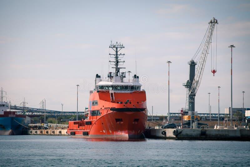 在港口设施和起重机前面的红色货物船 库存图片