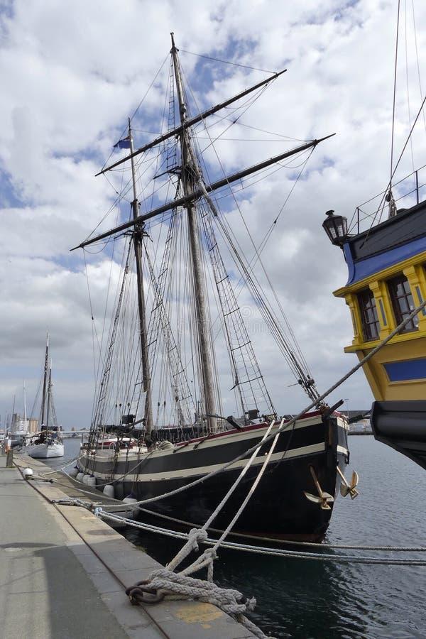 在港口靠码头的老木风船 免版税库存图片
