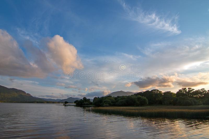 在港湾Leane [湖Leane的]日落与在凯利圆环的水lillies在基拉尼爱尔兰 免版税图库摄影