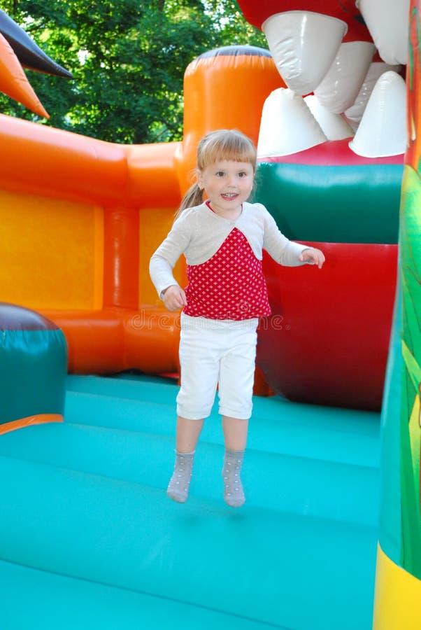 在游乐园,跳跃在一个可膨胀的幻灯片女孩。 免版税库存照片