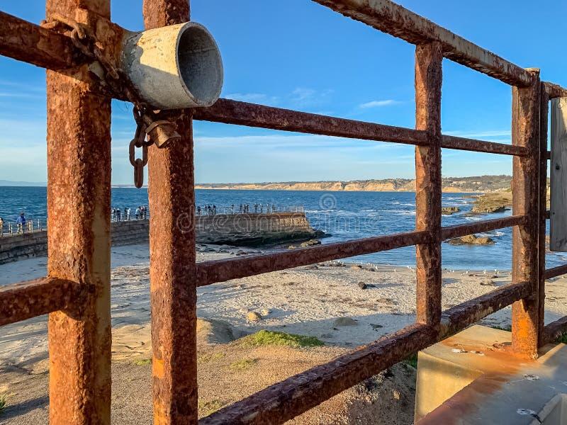 在游人前景的上锁的门俯视拉霍亚与海狮的码头的海滩小海湾 免版税库存图片