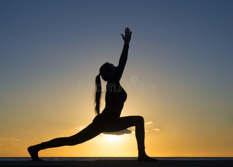 在游泳场和自然海滩的剪影年轻女人实践的姿势瑜伽在日落或日出 瑜伽和健康 免版税库存照片