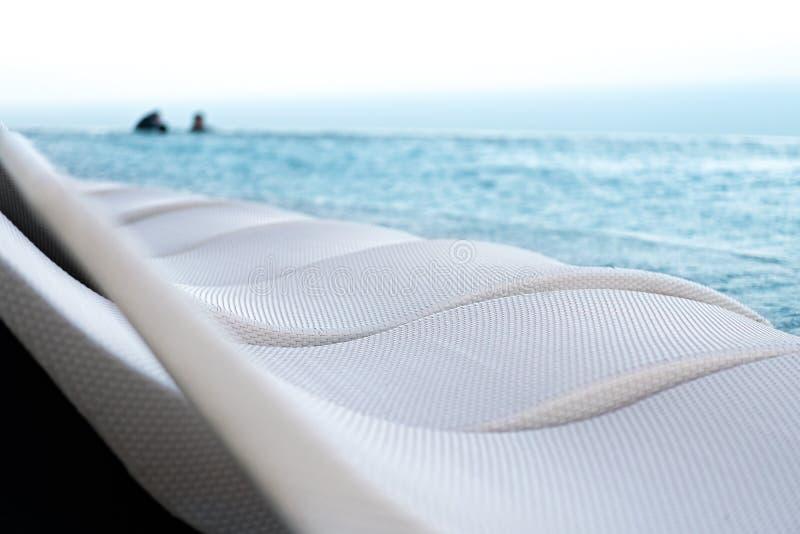 在游泳场旁边的放松的水池床 免版税库存照片