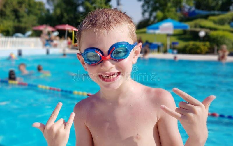 在游泳场的微笑的年轻男孩佩带的游泳的玻璃 免版税库存照片