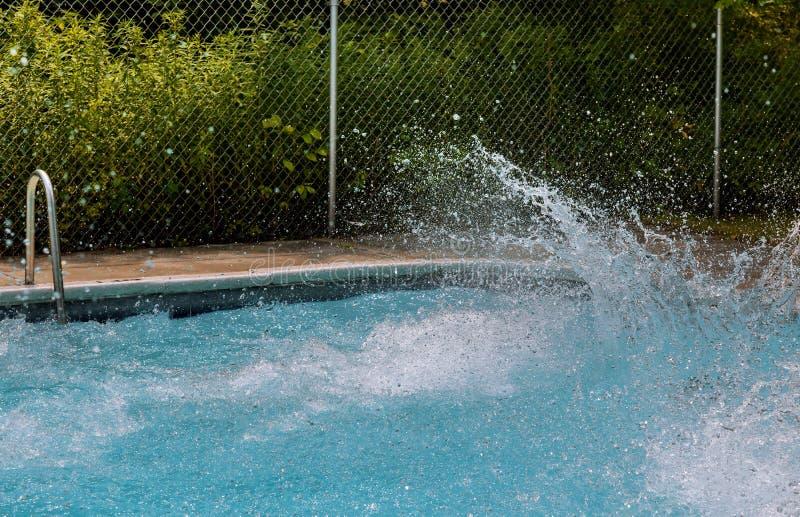 在游泳场的美丽的飞溅的水 免版税库存照片