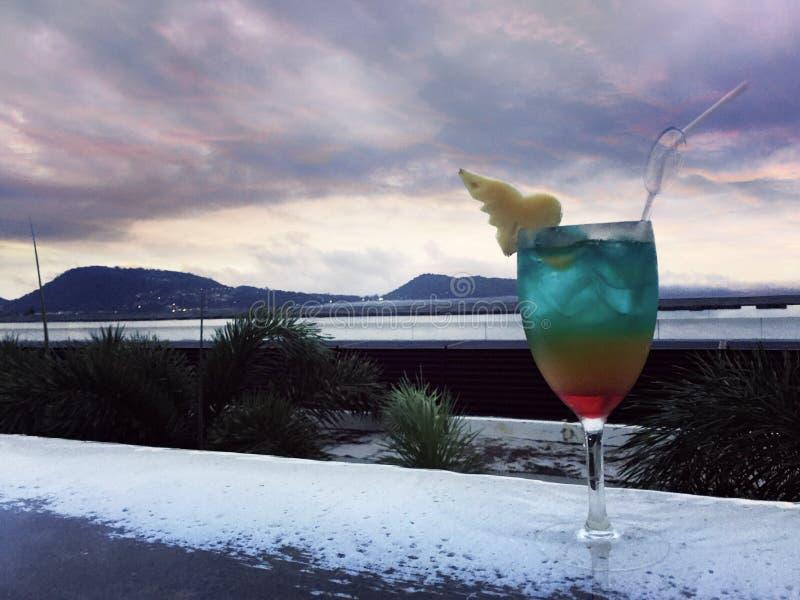 在游泳场边缘的五颜六色的鸡尾酒在海视图前面的 库存图片