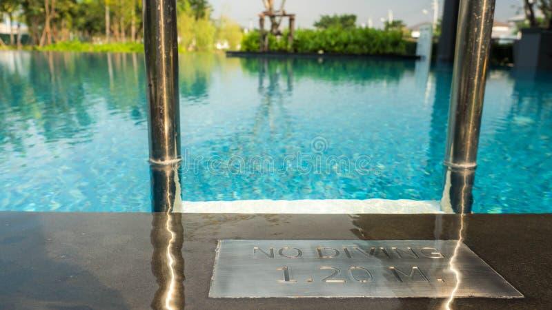 在游泳场/游泳场深度的没有潜水的标志征兆在水池边 库存图片