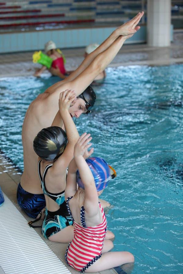 在游泳教训的孩子在室内游泳池 免版税库存照片