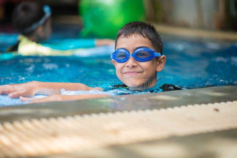 在游泳池室外活动的一点混合亚洲阿拉伯男孩游泳 库存照片