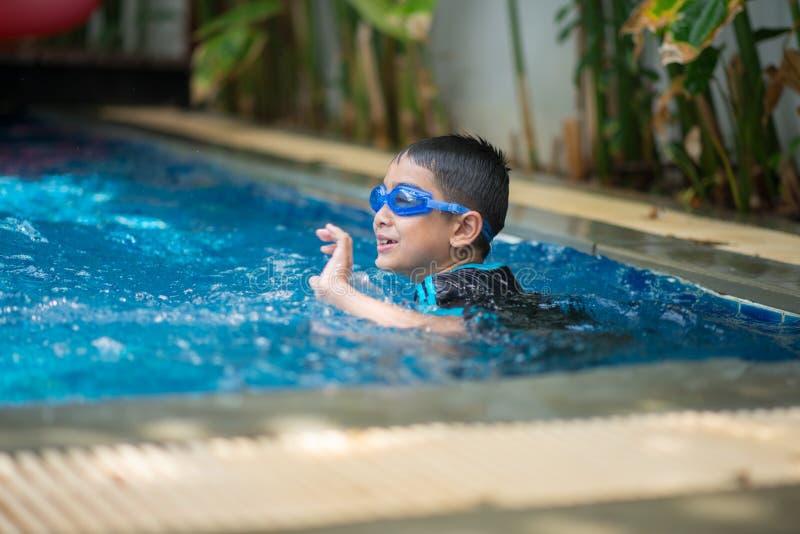 在游泳池室外活动的一点混合亚洲阿拉伯男孩游泳 免版税库存图片
