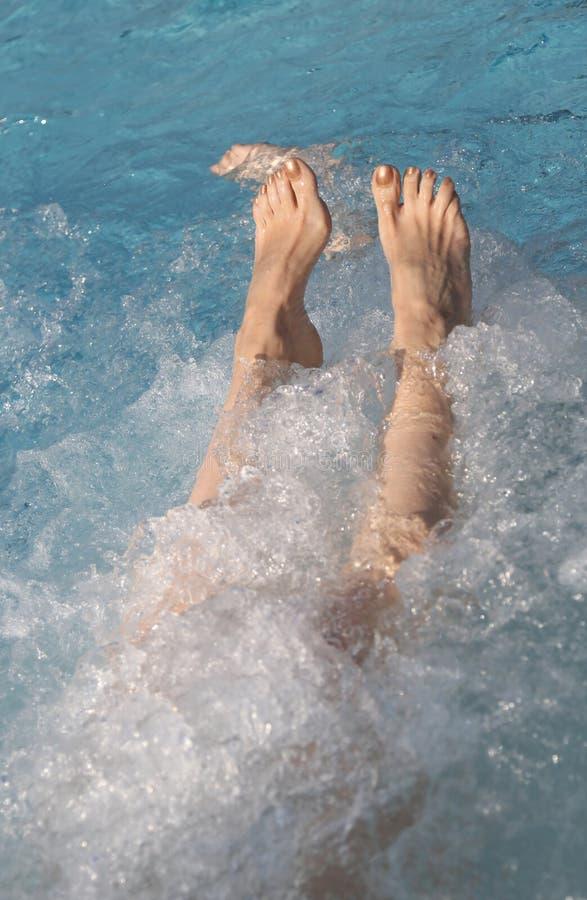 在游泳池放松妇女的脚 免版税库存照片