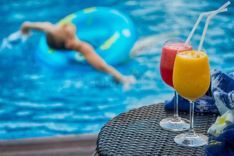 在游泳池旁边的两个鸡尾酒 妇女在背景中 库存图片