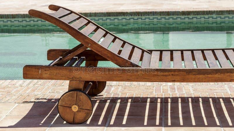 在游泳池旁边的太阳可躺式椅 夏令时 库存图片