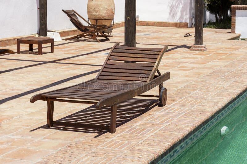 在游泳池旁边的木太阳可躺式椅 免版税库存图片