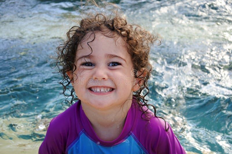 在游泳池的厚颜无耻的女孩微笑 库存照片