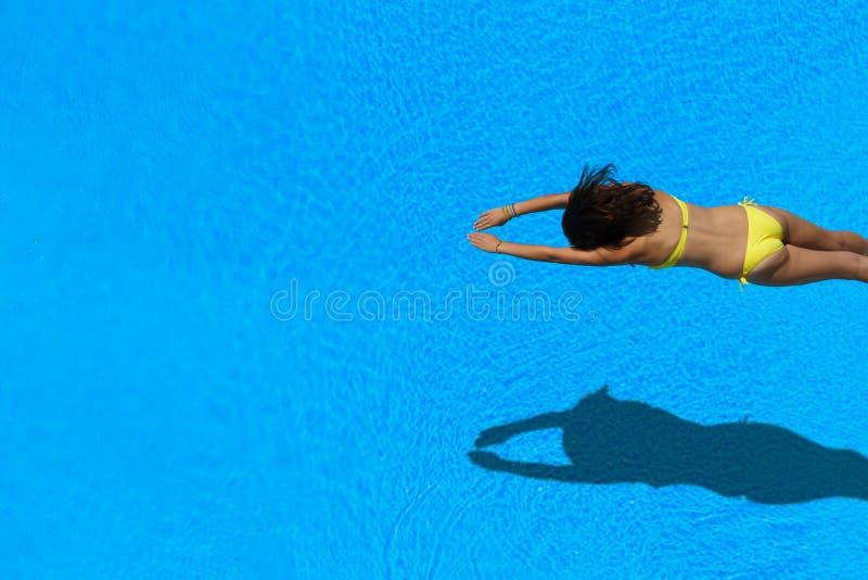 在游泳池的女孩潜水 免版税库存图片