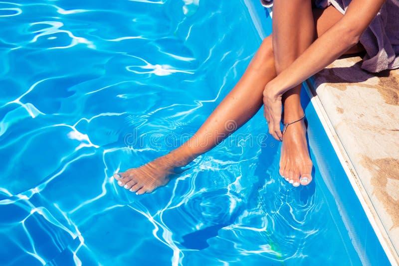 在游泳池的女性腿 免版税图库摄影