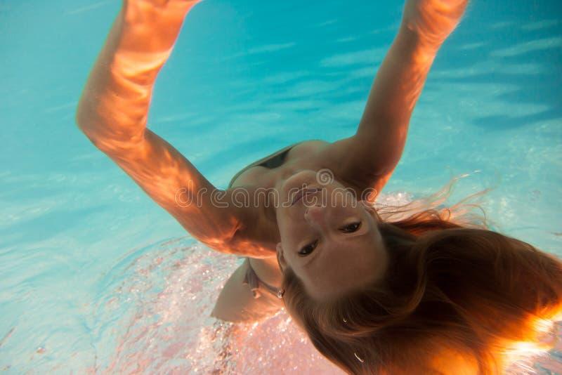 在游泳池的妇女undewater 免版税图库摄影