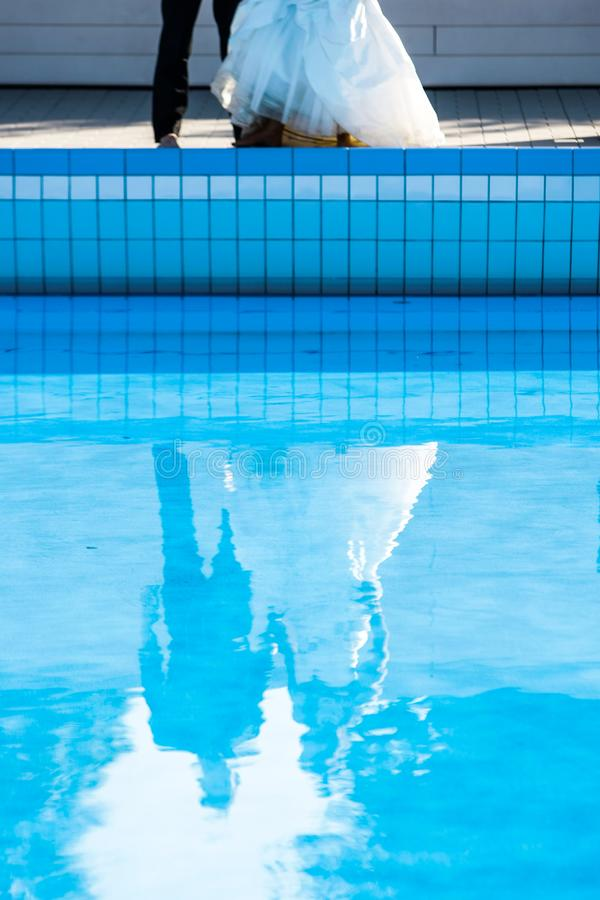 在游泳池的婚礼夫妇 免版税库存照片
