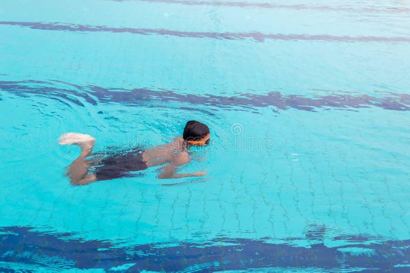在游泳池的年轻人游泳 在游泳池的适合的游泳者训练 免版税库存照片