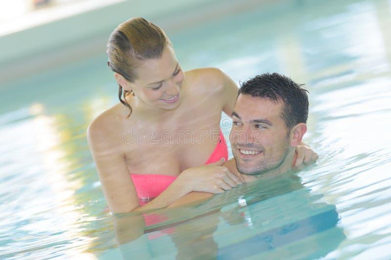 在游泳池的愉快的中年夫妇 库存图片