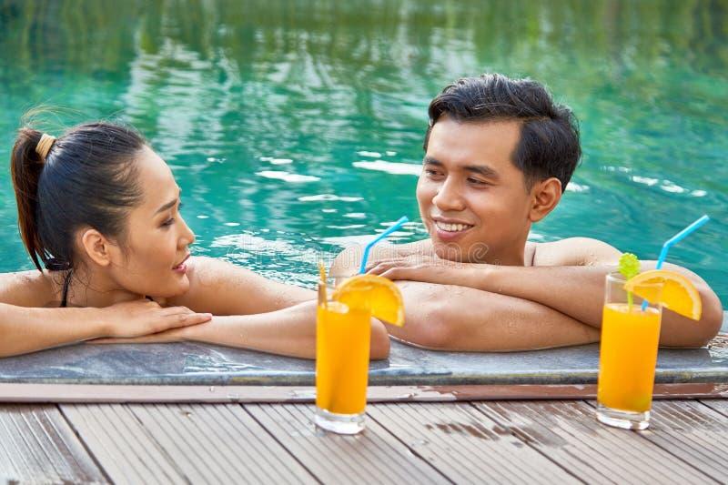 在游泳池的愉快的夫妇 库存图片