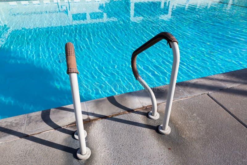 在游泳池的抓取条梯子,室外 图库摄影