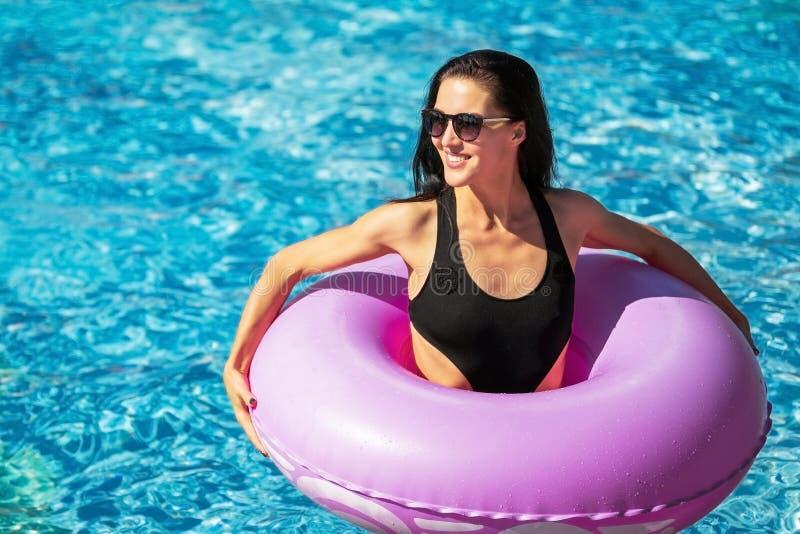 在游泳池的深色的夫人藏品游泳圆环 免版税库存照片