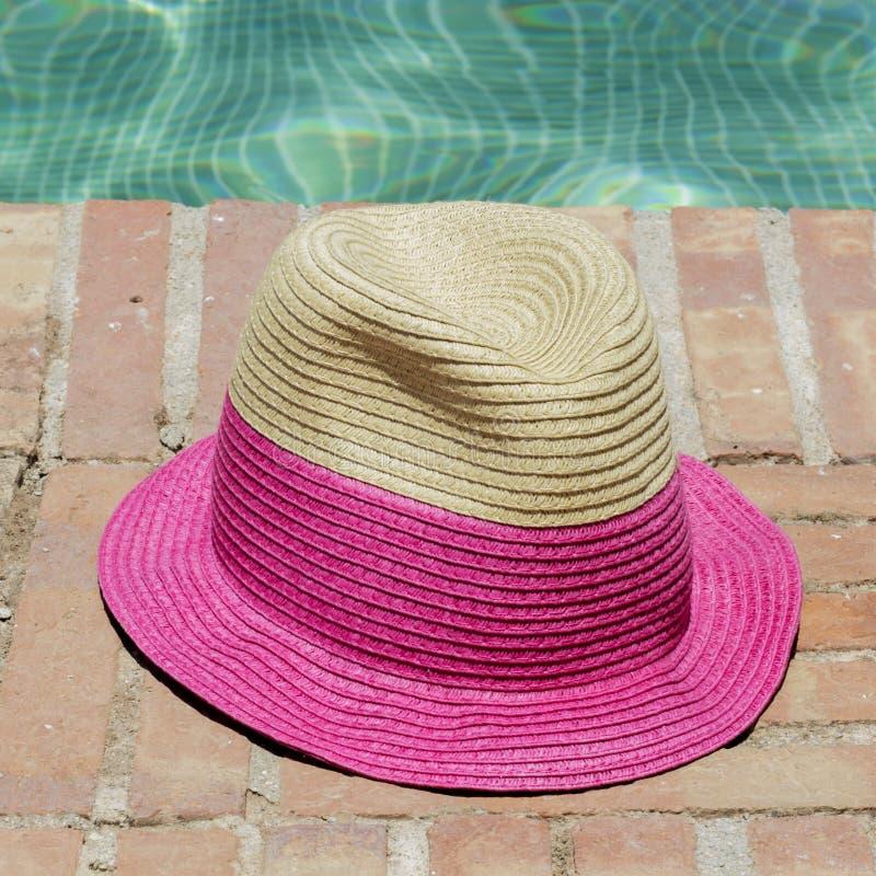 在游泳池的边缘的太阳帽子 免版税库存照片
