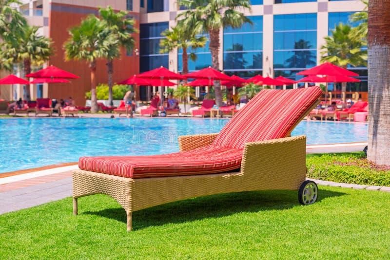 在游泳池的轻便折叠躺椅 免版税库存照片