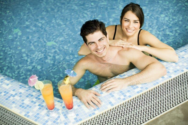 在游泳池的年轻夫妇 库存照片