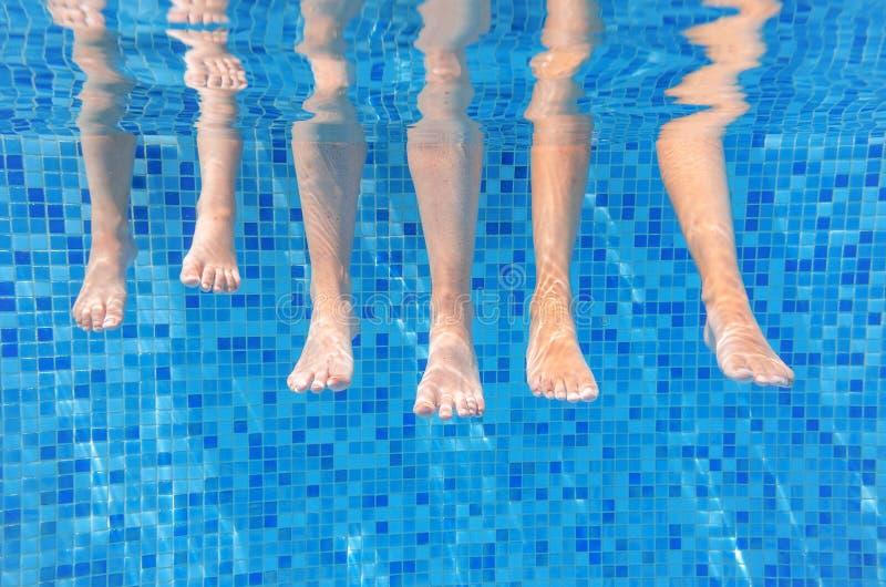 在游泳池的滑稽的水下的家庭腿,在水观点的母亲下和孩子、假期和体育 免版税图库摄影