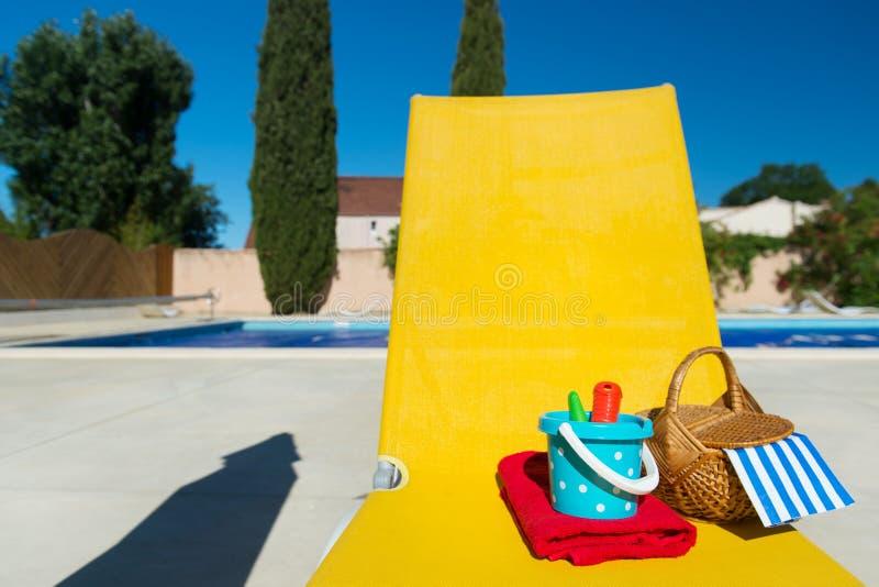 在游泳池的黄色床 库存图片