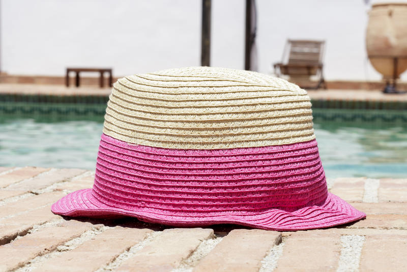 在游泳池边缘的太阳帽子 库存照片