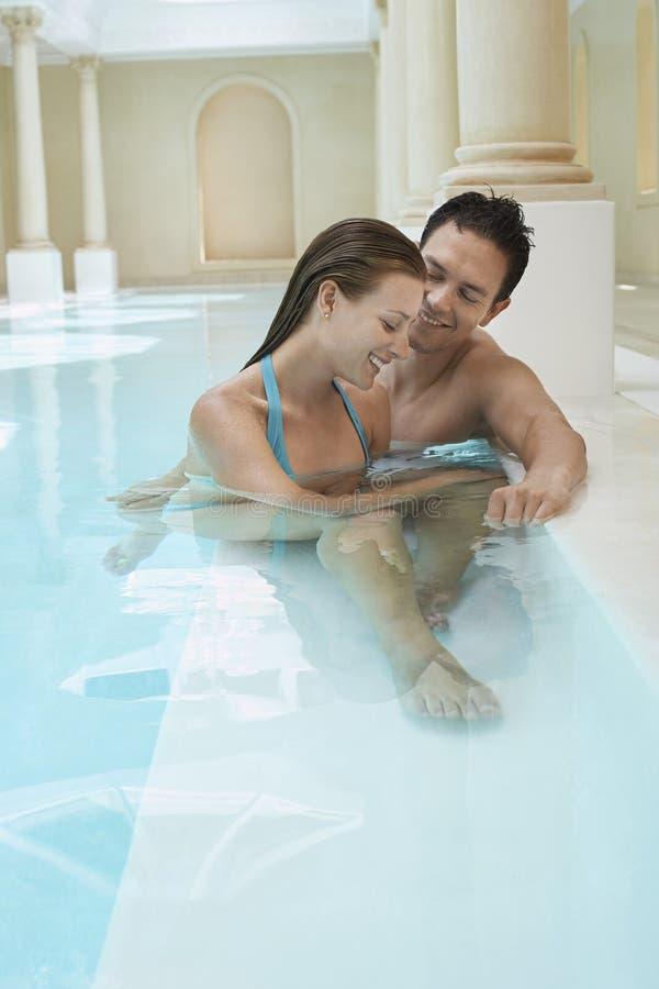 在游泳池边缘的浪漫夫妇  图库摄影